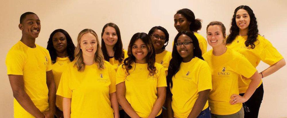 UNCG team in yellow shirts.